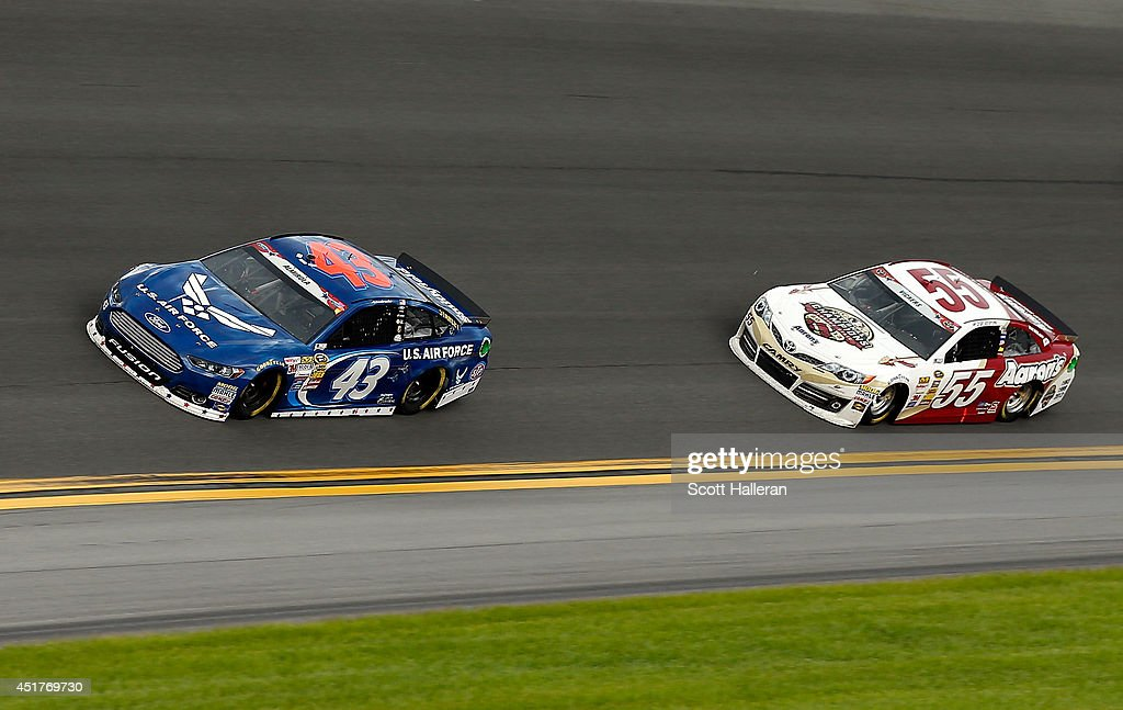 Aric Almirola, driver of the #43 United States Air Force Ford, leads Brian Vickers, driver of the #55 Aaron's/FSU National Championship Toyota, during the NASCAR Sprint Cup Series Coke Zero 400 at Daytona International Speedway on July 6, 2014 in Daytona Beach, Florida.