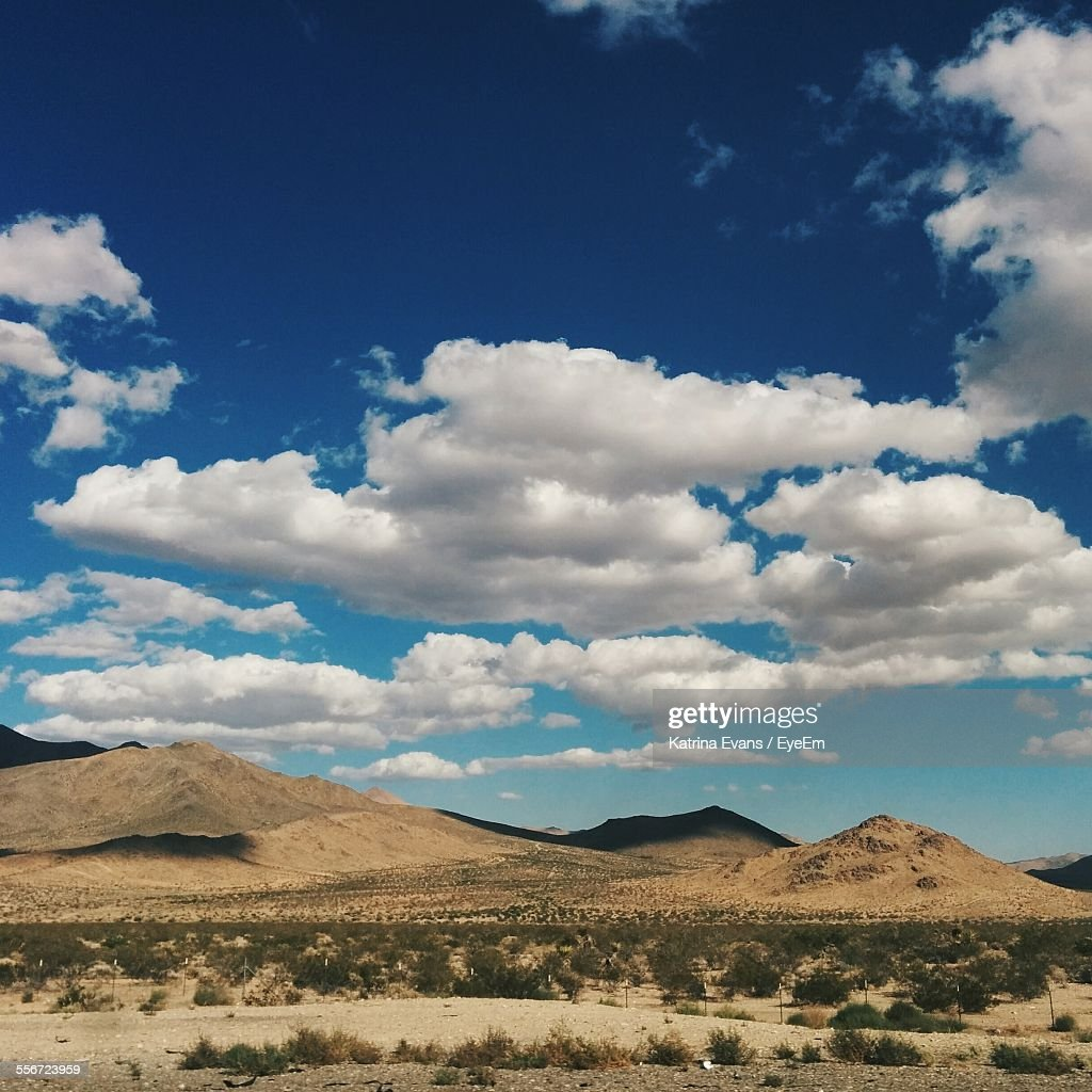 Arid Landscape And Mountains Against Blue Sky