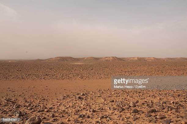 Arid Landscape And Mountains Against Clear Sky