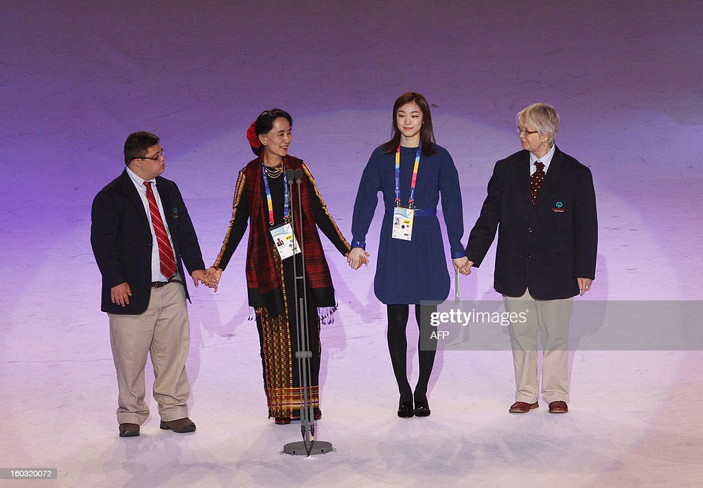 Ariel Ary (R), Special Olympics Global Messenger from Canada, Myanmar opposition leader Aung San Suu Kyi (2nd L), Vancouver Olympics 2010 women's figure skating gold medalist Kim Yu-na (2nd R) of South Korea, Caroline Verdenal, Special Olympics Global Messenger of France and and unidentified representative attend the opening of the Special Olympics World Winter Games in Pyeongchang, about 180 km (112 miles), east of Seoul on January 29, 2013. The democracy leader and Nobel peace laureate was a guest of honour at the opening of the Special Winter Olympics in the northeastern mountain resort of Pyeongchang -- site of the full 2018 Winter Games. AFP PHOTO / Ahn Young-joon / POOL