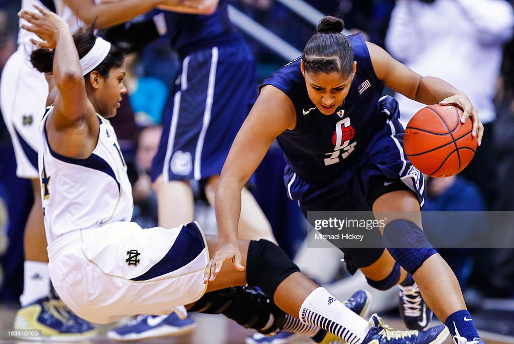 Ariel Braker #44 of the Notre Dame Fighting Irish falls as Kaleena Mosqueda-Lewis #23 of the Connecticut Huskies dribbles around her at Purcel Pavilion on March 4, 2013 in South Bend, Indiana. Notre Dame defeated Connecticut 96-87 in triple overtime to win the Big East regular season title.