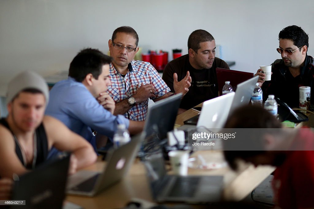 Ariel Martinez (2nd L) and Karel Cardona work on creating a message and news provider for cell phones in Cuba so people living on the island would have access during the Hackathon for Cuba event on February 1, 2014 in Miami, Florida. The hackathon brought together experts and programmers to devise innovative technology solutions aimed at strengthening communications and information access in Cuba. The event is organized by Roots of Hope with support from the John S. and James L. Knight Foundation.