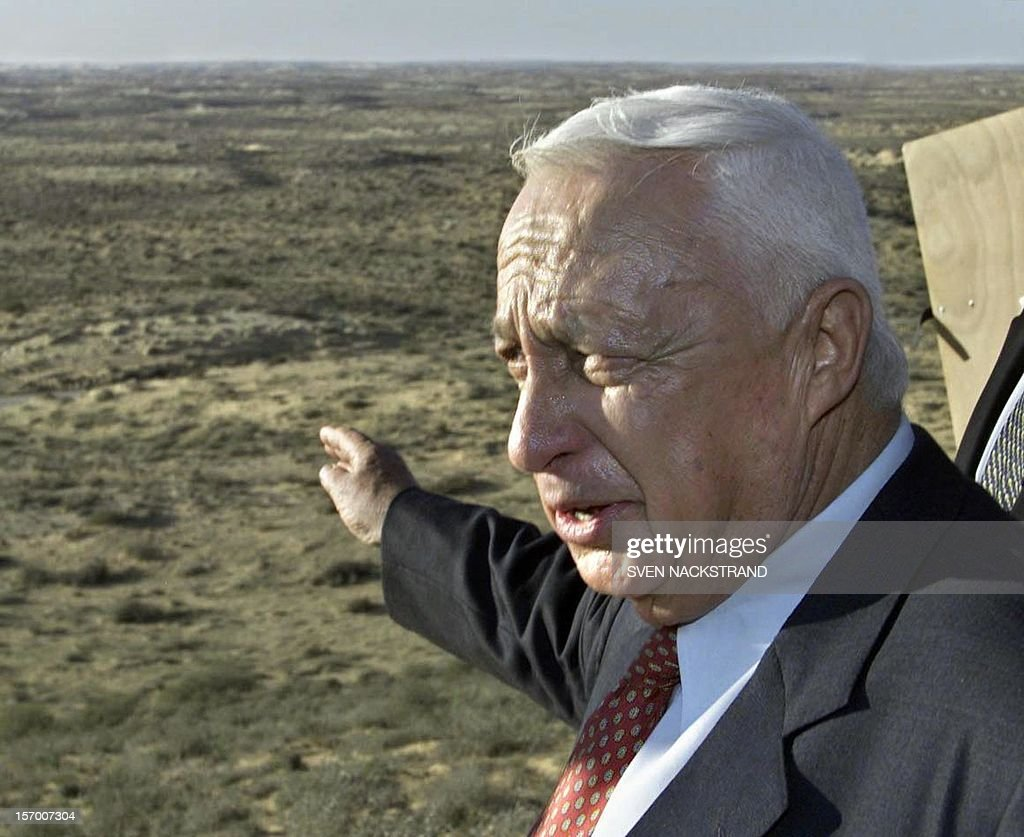 Ariel Sharon, the rightwing Likud's candidate for the prime minister's post, points to the Halutza area during a tour near Moshav Kemhin in the Negev Desert 15 January 2001. Sharon said during the visit, that the sand dunes of Halutza, that Prime Minister Ehud Barak has offered to the Palestinians as a substitute for areas in the West Bank, will never be given away as they are needed for the growth of Israel's Jewish population. Sharon is the frontrunner in the 06 February prime ministerial elections. AFP PHOTO/Sven NACKSTRAND