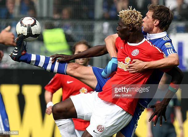 Aristide Bance of Mainz is challenged by Benedikt Hoewedes of Schalke during the Bundesliga match between FSV Mainz 05 and FC Schalke 04 at the...