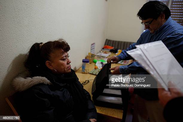 Aristides Apolo gives court papers to an activist as Mercedes Pincay waits for her eviction to take place on December 15 2014 in Madrid Spain The...