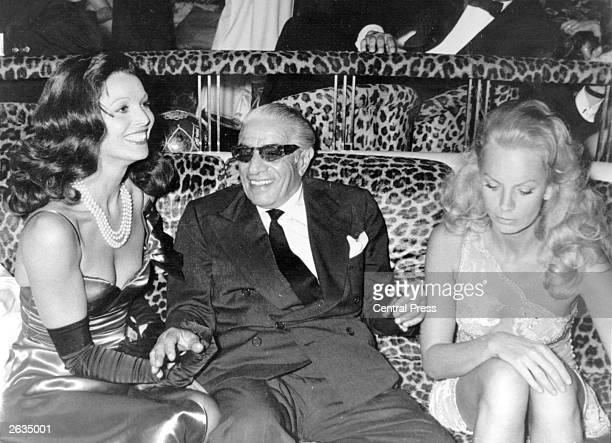 Aristotle Onassis wears his trademark 'shades' while partying with Elsa Martinelli in Paris