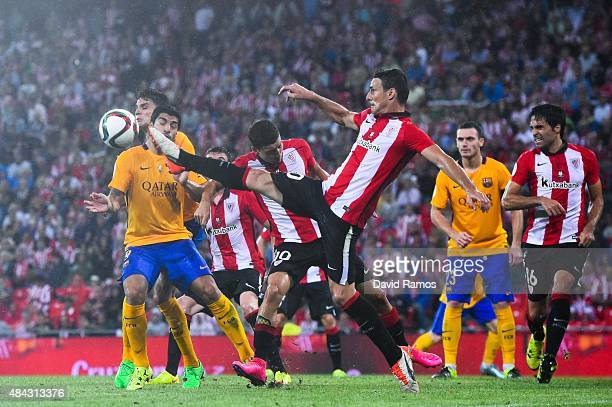 Aritz Aduriz of Athletic Club clears the ball under pressure from Luis Suarez of FC Barcelona during the Spanish Super Cup first leg match between FC...