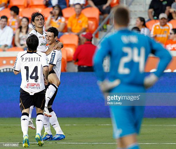 Aritz Aduriz of Valencia celebrates with Tino Costa and Pablo Piatti after scoring on goalkeeper Tyler Deric of the Houston Dynamo at BBVA Compass...