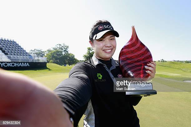 Ariya Jutanugarn of Thailand poses for a simulated 'Selfie' with the trophy on the 18th hole after winning the Yokohama Tire Classic on May 08 2016...
