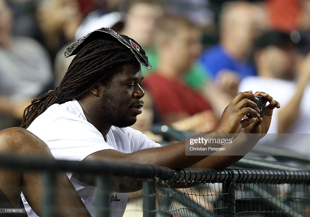 Arizona Cardinals first round draft pick Jonathan Cooper takes photos during the MLB game between the Arizona Diamondbacks and the Miami Marlins at Chase Field on June 17, 2013 in Phoenix, Arizona.