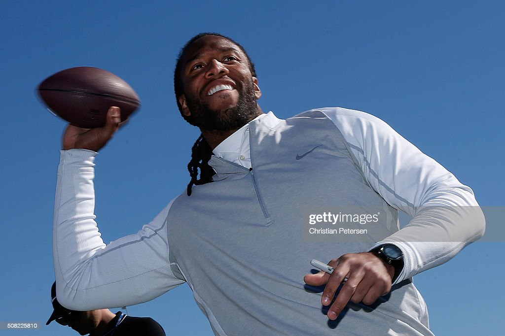 Arizona Cardinals wide receiver Larry Fitzgerald throws an autographed ball to fans on the 18th green following the pro-am for the the Waste Management Phoenix Open at TPC Scottsdale on February 3, 2016 in Scottsdale, Arizona.