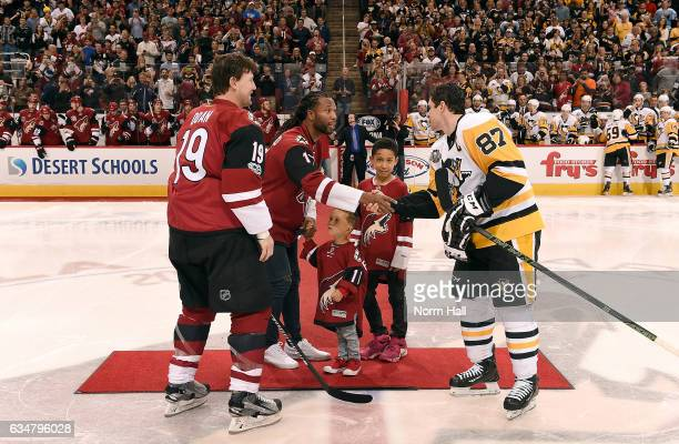 Arizona Cardinals wide receiver Larry Fitzgerald with his sons Apollo and Devin shakes hands with Shane Doan of the Arizona Coyotes and Sidney Crosby...