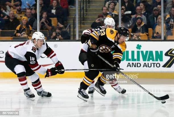 Arizona Coyotes center Christian Dvorak hooks Boston Bruins left wing Brad Marchand on the break away attempt during a game between the Boston Bruins...