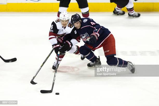 Arizona Coyotes defenseman Jakob Chychrun and Columbus Blue Jackets defenseman Scott Harrington battle for the puck during the first period in a game...