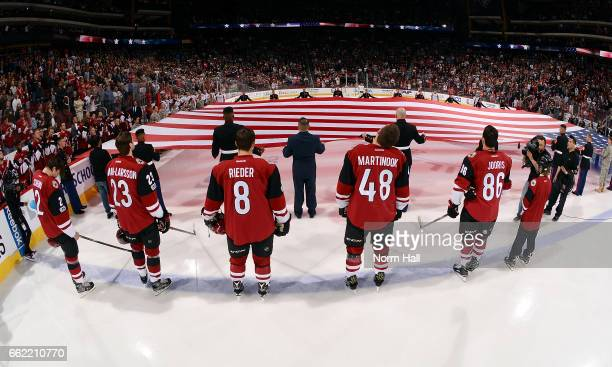 Arizona Coyotes players stand for the National Anthem as a large american flag is held across the ice as part of Pat Tillman Military Appreciation...