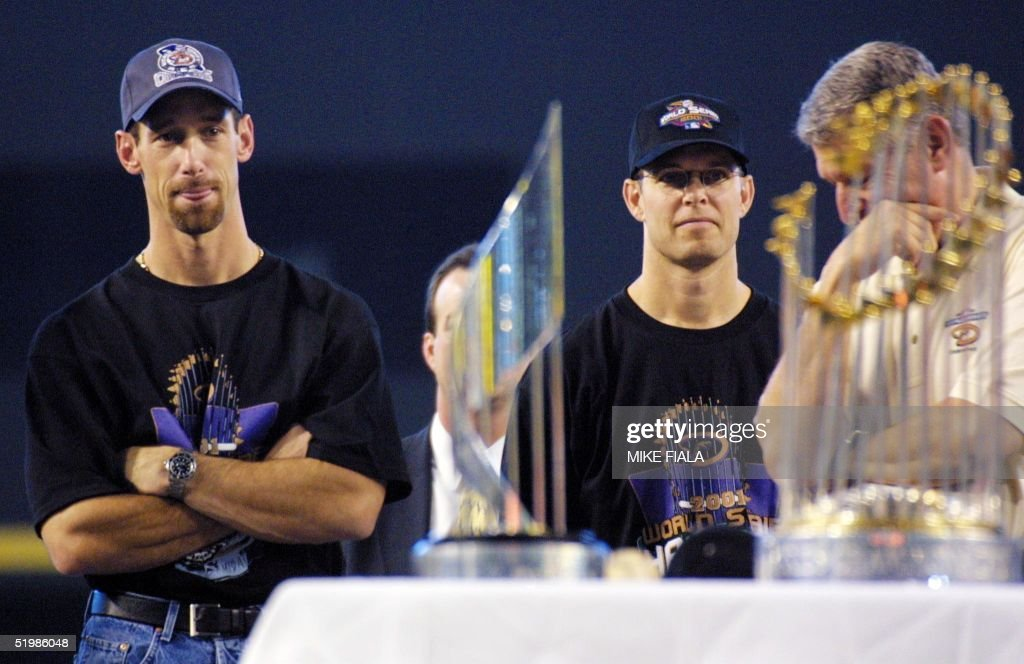 Arizona Diamondbacks' Luis Gonzalez (L), Jay Bell (C) and managing general partner Jerry Colangelo (R) attend a victory rally 07 November 2001 at Bank One Ballpark in Phoenix, AZ. In the foreground is the World Series trophy (R) and the MVP trophy presented to Diamondbacks' Randy Johnson and Curt Schilling. Gonzalez hit the winning RBI and Bell scored the winning run in game seven against the New York Yankees to win the 2001 World Series.