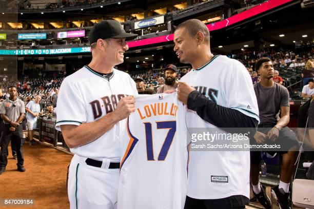 Arizona Diamondbacks manager Torey Lovullo exchanges jerseys with Phoenix Suns coach Earl Watson during a pregame recognition on Suns Night prior to...