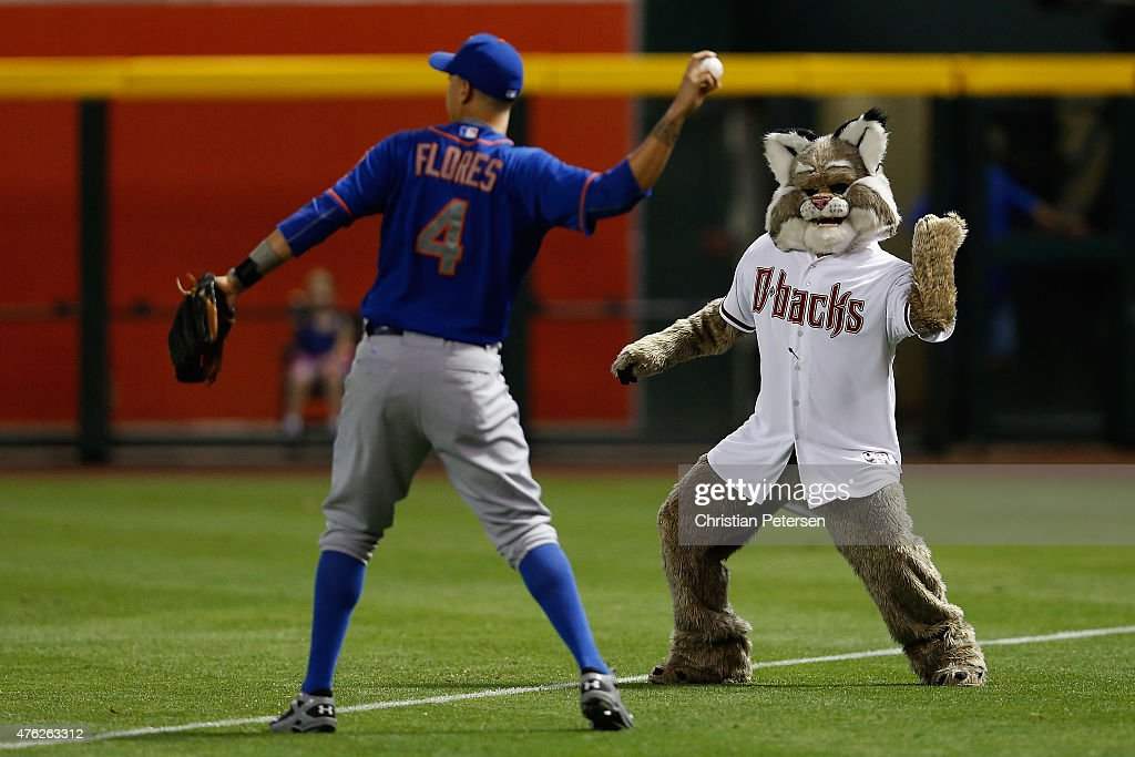 Arizona Diamondbacks mascot D Baxter the Bobcat jokes with Wilmer Flores of the New York Mets as he warms up before the MLB game against the Arizona...