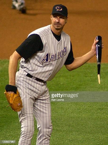 Arizona Diamondbacks pitcher Randy Johnson tosses the broken bat of Colorado Rockies Greg Zaun back towards the dugout after Zaun got a hit in the...