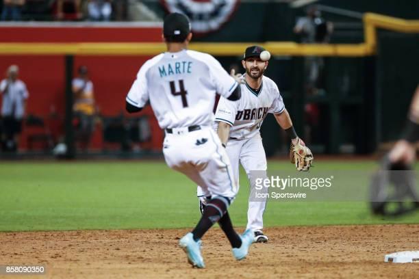 Arizona Diamondbacks second baseman Daniel Descalso tosses the ball to Arizona Diamondbacks shortstop Ketel Marte for the final out of the MLB...