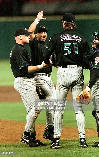 Arizona Diamondbacks shortstop Tony Womack gives a high five to ace pitcher Randy ''The Big Unite' Johnson as teammates Matt Williams and catcher...