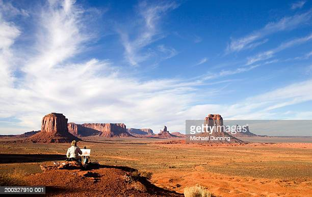 USA, Arizona, Monument Valley, woman painting with easel, rear view