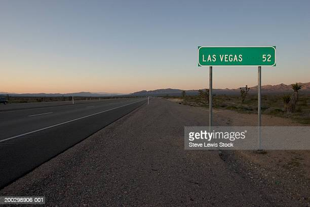 USA, Arizona, Route 93, road sign 52 miles from Las Vegas, sunset