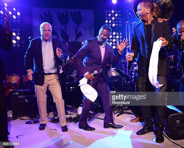 Arizona Senator John McCain and Jamie Foxx dance onstage at Apollo in the Hamptons at The Creeks on August 16 2014 in East Hampton New York