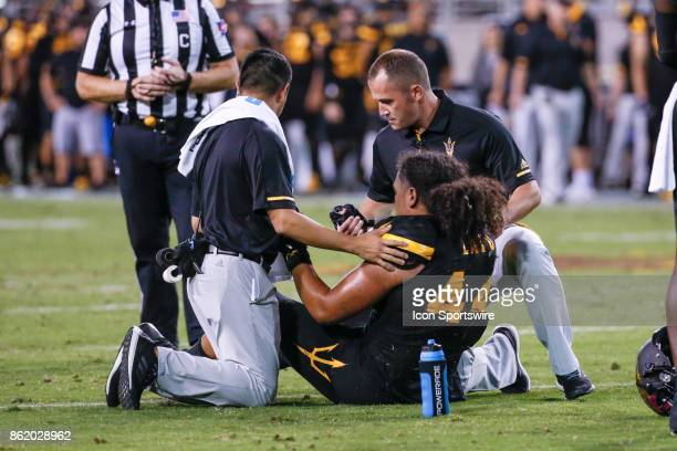 Arizona State Sun Devils linebacker Alani Latu is attended to by trainers after being injured during the college football game between the Washington...