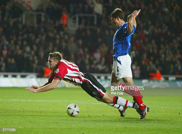 Arjan De Zeeuw of Portsmouth brings down James Beattie of Southampton for a penalty during the Carling Cup fourth round match between Southampton and...