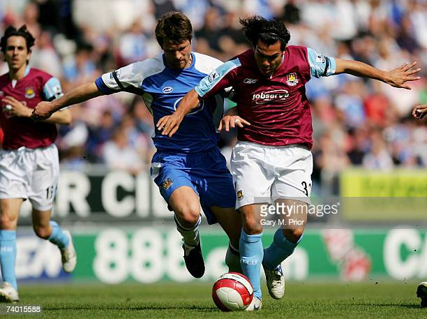 Arjan De Zeeuw of Wigan and Carlos Tevez of West Ham battle for the ball during the Barclays Premiership match between Wigan Athletic and West Ham...