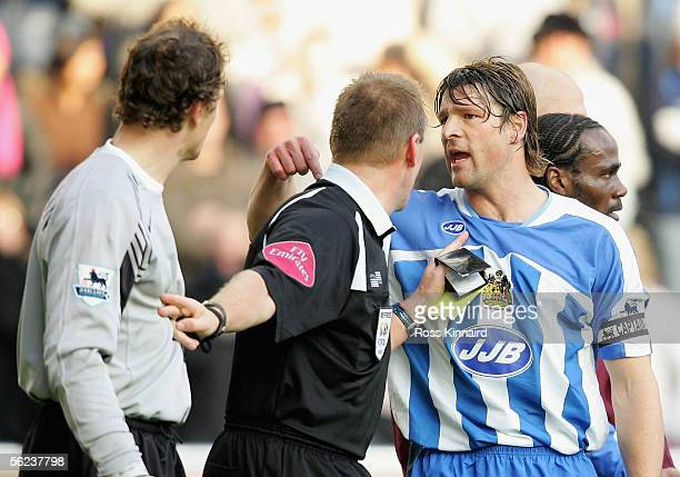 Arjan DeZeeuw of Wigan clashes with Jens Lehmann of Arsenal during the Barclays Premiership match between Wigan Athletic and Arsenal at the JJB...