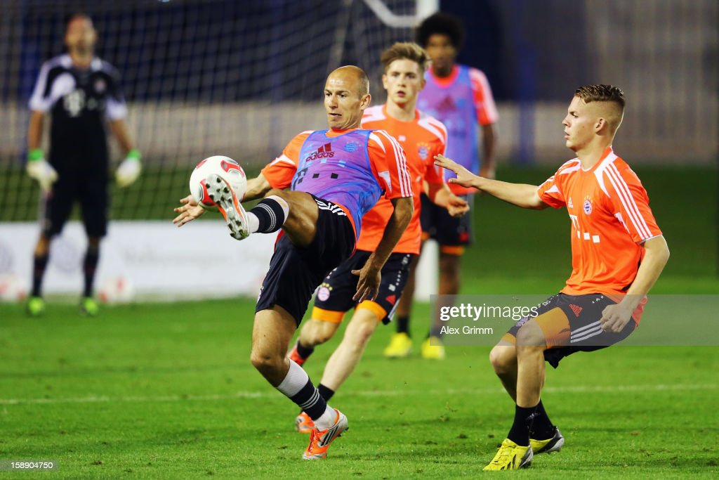 <a gi-track='captionPersonalityLinkClicked' href=/galleries/search?phrase=Arjen+Robben&family=editorial&specificpeople=194740 ng-click='$event.stopPropagation()'>Arjen Robben</a> (L) is challenged by Daniel Wein during a Bayern Muenchen training session at the ASPIRE Academy for Sports Excellence on January 3, 2013 in Doha, Qatar.