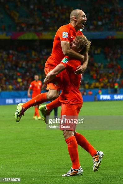 Arjen Robben jumps into the arms of Dirk Kuyt of the Netherlands as they celebrate victory in a penalty shootout during the 2014 FIFA World Cup...