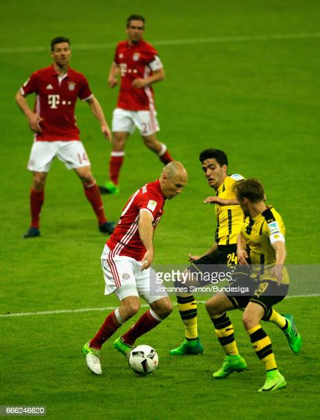 Arjen Robben of Bayern and Mikel Merino and Marcel Schmelzer of Dortmund fight for the ball during the Bundesliga match between Bayern Muenchen and...
