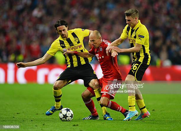 Arjen Robben of Bayern Muenchen battles with Neven Subotic and Lukasz Piszczek of Borussia Dortmund during the UEFA Champions League final match...