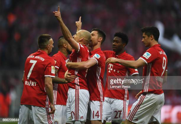 Arjen Robben of Bayern Muenchen celebrates scoring his sides third goal with his Bayern Muenchen team mates during the Bundesliga match between...
