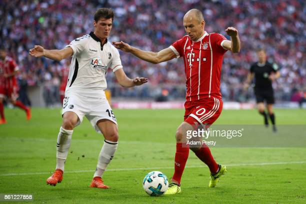 Arjen Robben of Bayern Muenchen fights for the ball with Pascal Stenzel of Freiburg during the Bundesliga match between FC Bayern Muenchen and...