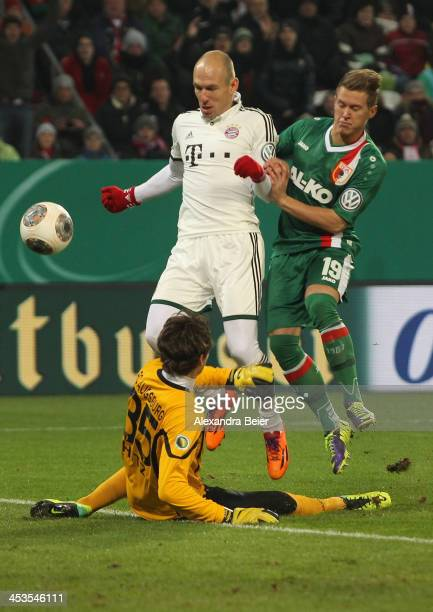 Arjen Robben of Bayern Muenchen fscores his first goal against Matthias Ostrzolek and goalkeeper Marwin Hitz of Augsburg during their DFB Cup round...