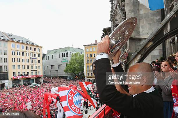 Arjen Robben of Bayern Muenchen holds the German Championship winners trophy as the team celebrate winning the German Championship title on the town...