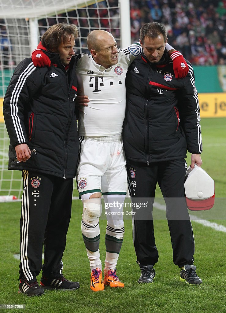 Arjen Robben (C) of Bayern Muenchen is assisted by team doctors after he was injured during their DFB Cup round of 16 match between FC Augsburg and FC Bayern Muenchen at SGL Arena on December 4, 2013 in Augsburg, Germany.