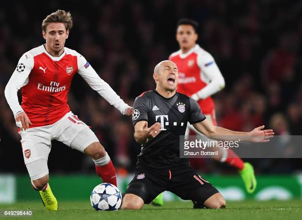 Arjen Robben of Bayern Muenchen is challenged by Nacho Monreal of Arsenal during the UEFA Champions League Round of 16 second leg match between...
