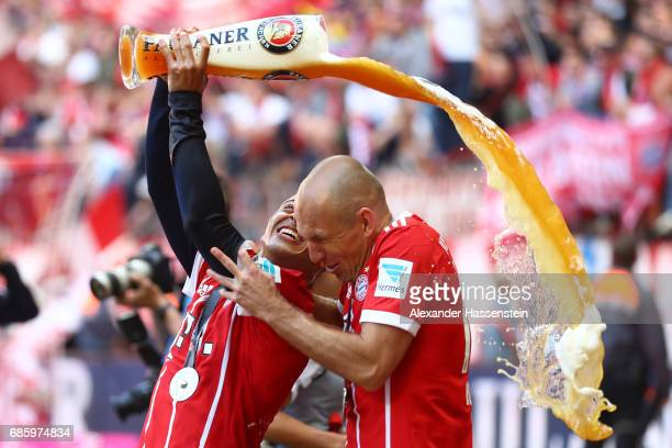 Arjen Robben of Bayern Muenchen is showered in beer by teammate Thiago of Bayern Muenchen following the Bundesliga match between Bayern Muenchen and...