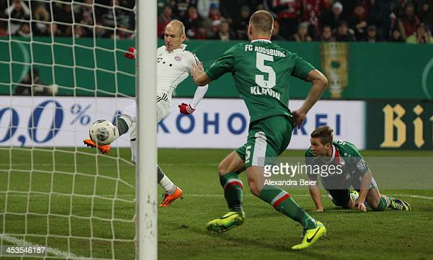 Arjen Robben of Bayern Muenchen scores his first goal against Matthias Ostrzolek and Ragnar Klavan of Augsburg during their DFB Cup round of 16 match...