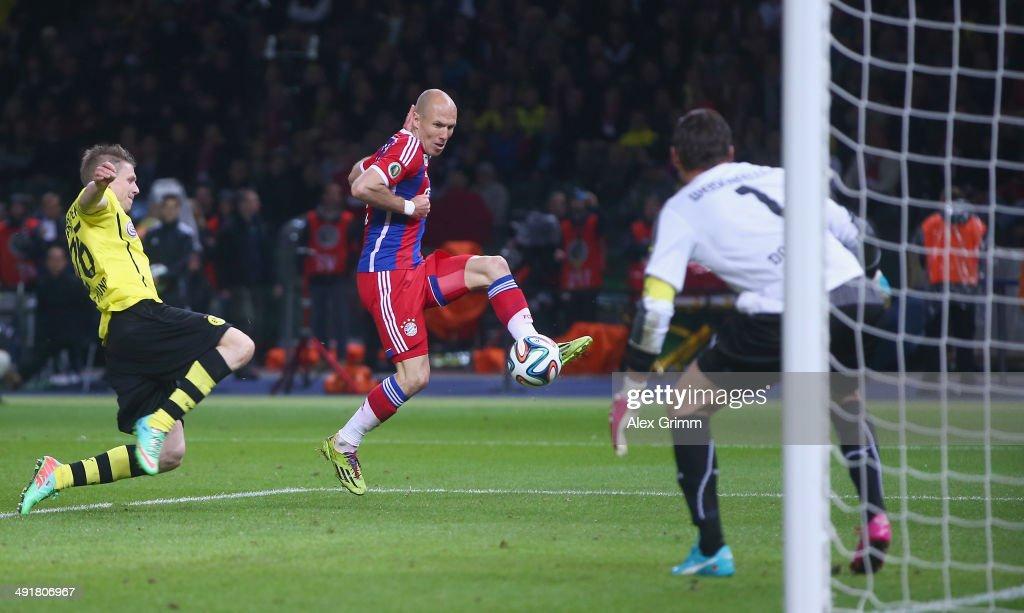 Arjen Robben of Bayern Muenchen scores his team's first goal against goalkeeper Roman Weidenfeller and Lukasz Piszczek of Borussia Dortmund during...