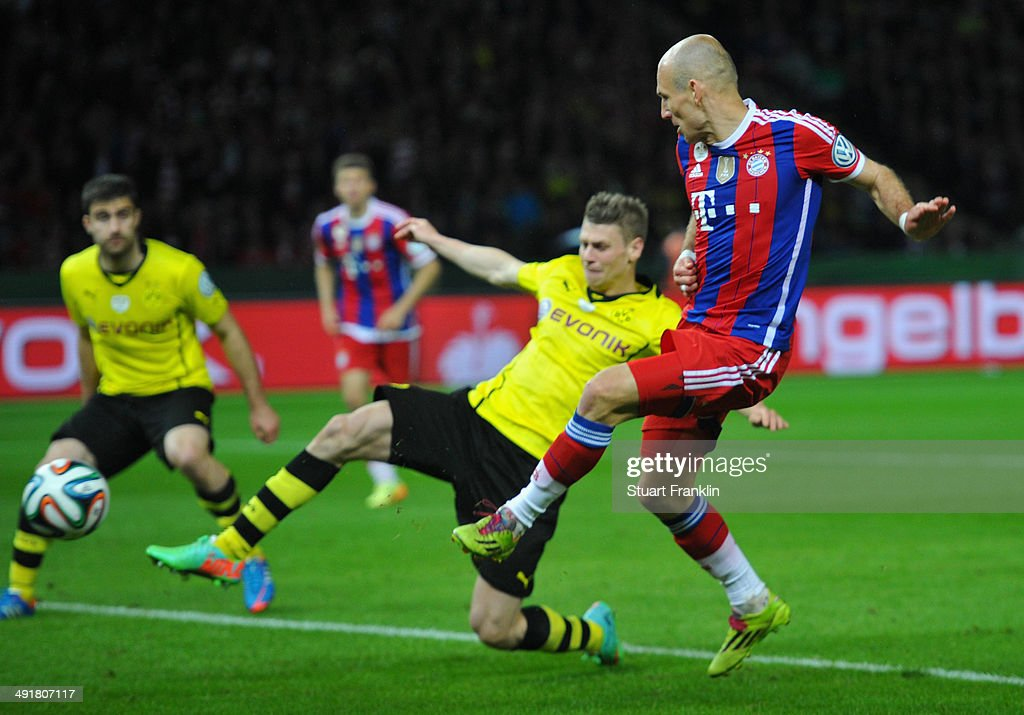 Arjen Robben of Bayern Muenchen scores his team's first goal against Lukasz Piszczek of Borussia Dortmund during the DFB Cup Final match between...