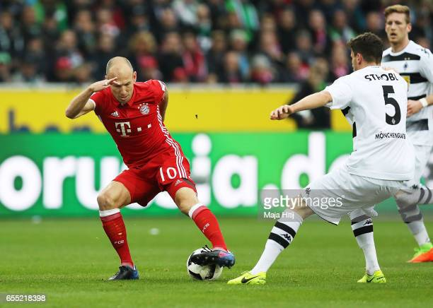 Arjen Robben of Bayern Munich is challenged by Tobias Strobl of Borussia Moenchengladbach during the Bundesliga match between Borussia...