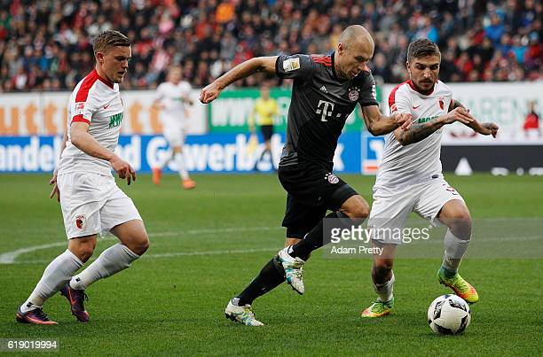 Arjen Robben of Bayern Munich is tackled by Kostas Stafylidis of Augsburg during the Bundesliga match between FC Augsburg and Bayern Muenchen at WWK...