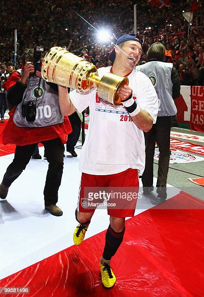 Arjen Robben of Bayern presents the trophy after winning during the DFB Cup final match between SV Werder Bremen and FC Bayern Muenchen at Olympic...