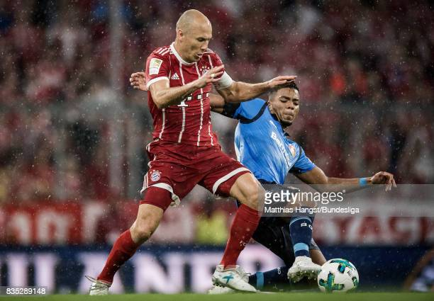 Arjen Robben of FC Bayern Muenchen and Benjamin Henrichs of Leverkusen compete for the ball during the Bundesliga match between FC Bayern Muenchen...